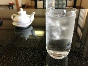 机の上の冷たい水が入ったコップ